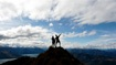 silhouette of people on the mountain peak