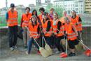Group of students in orange vests doing volunteer work in the streets