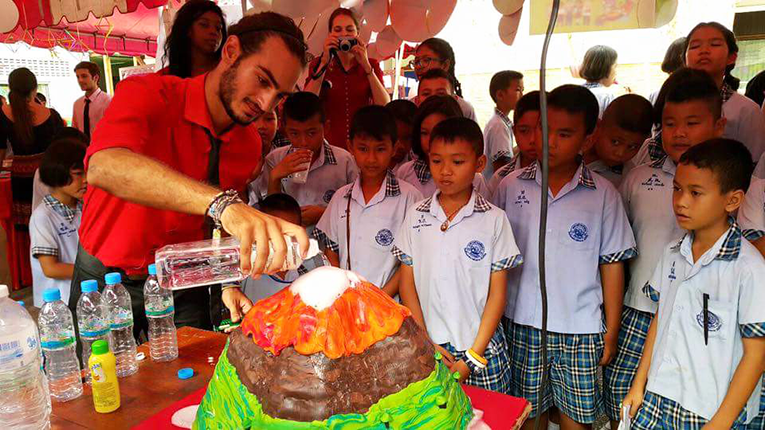 International teacher conducting a volcano experiment with students