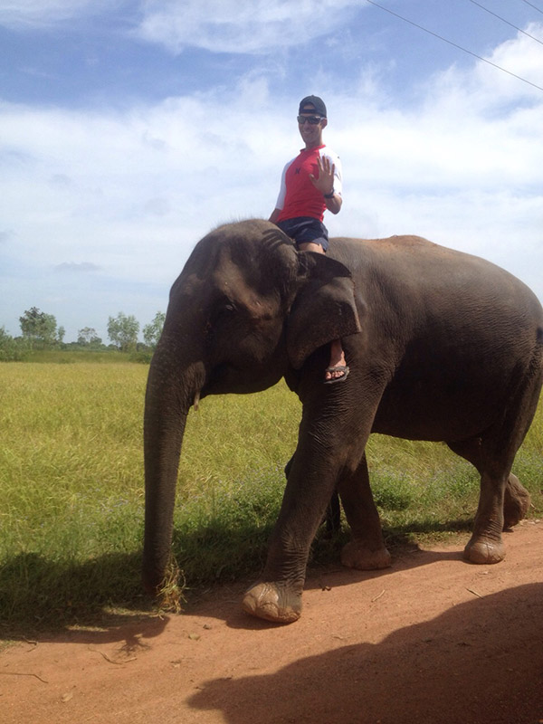 Volunteer riding an elephant in Thailand