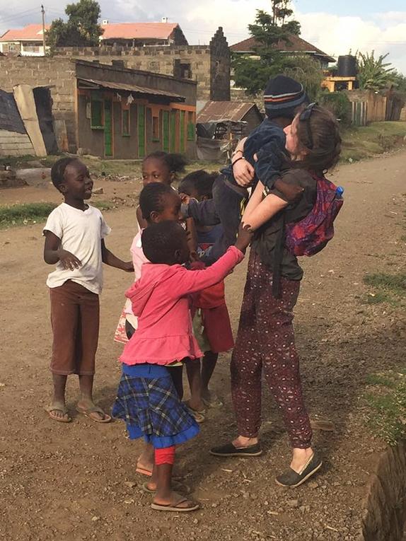 Children at the Hilton Dump in Kenya hugging an international volunteer