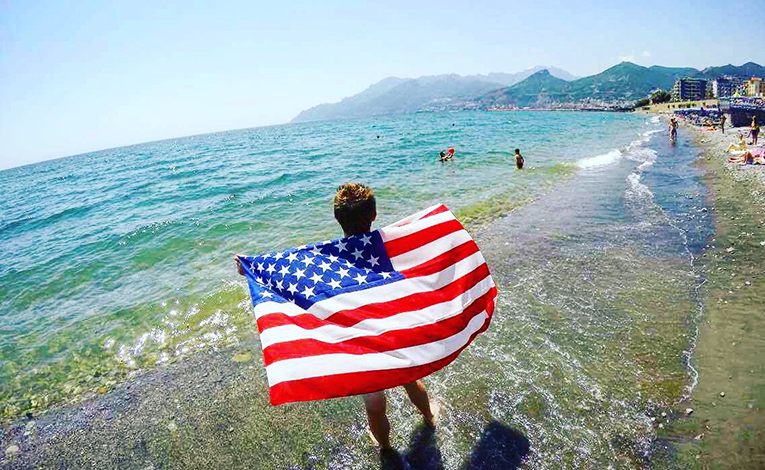 Man holding an American flag standing on a beach in Salerno, Italy