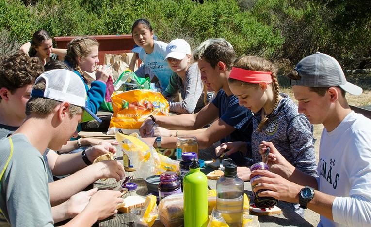 Teenage volunteers preparing bagged lunches