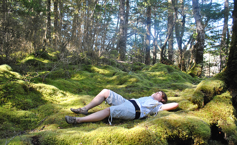 Woman laying in the grass in the woods