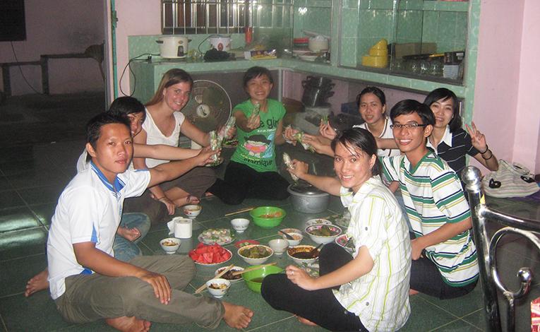 International teacher eating dinner with Vietnamese students