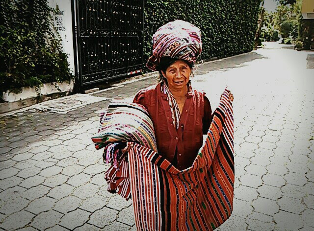 A Guatemalan woman sells locally woven garments on the street