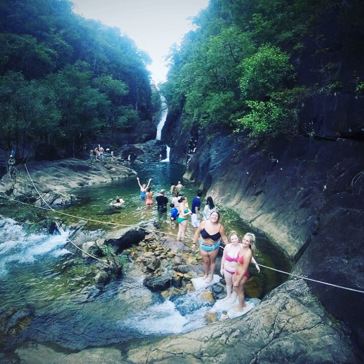 Tourists exploring a waterfall in Thailand