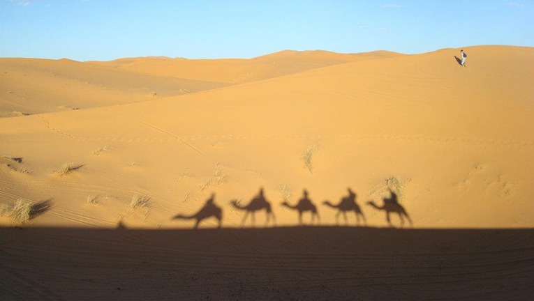 Shadows of camel trek participants in Morocco