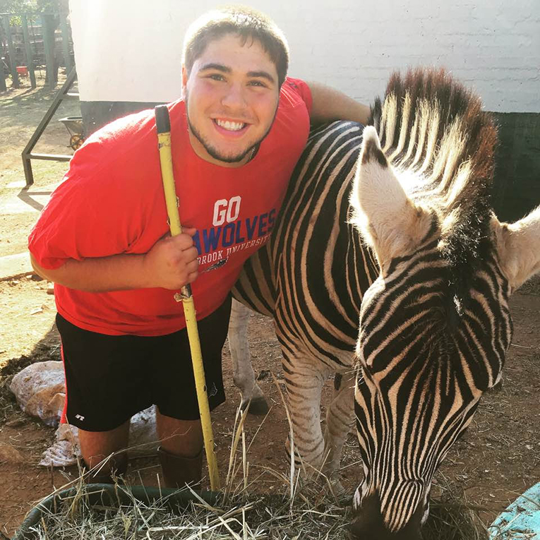 Volunteer with zebra in South Africa