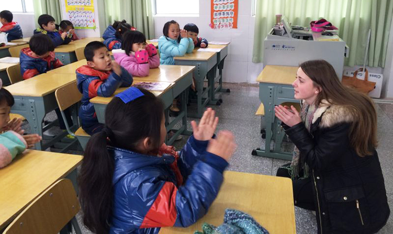 Foreign teacher clapping with local students in China