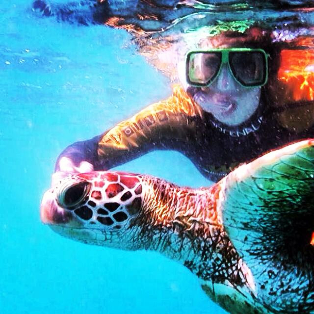 Girl swimming with a sea turtle in Queensland, Australia