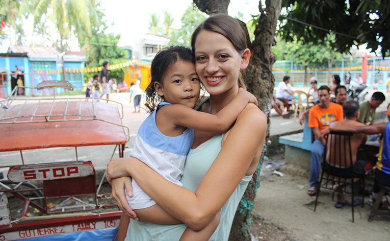 Volunteer holding local girl in the Philippines