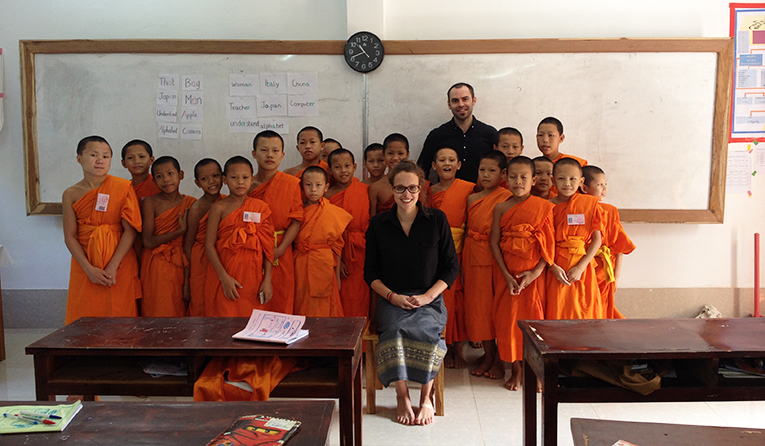 Volunteer teacher with class of novice buddhist monks in Laos