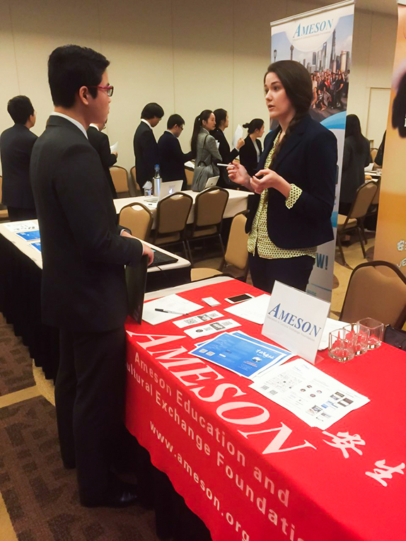Ameson Education and Cultural Exchange Foundation staff member talking to a student at the Georgetown China Business Expo
