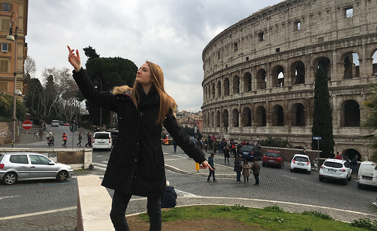 Girl posing in front of the Colosseum in Rome, Italy
