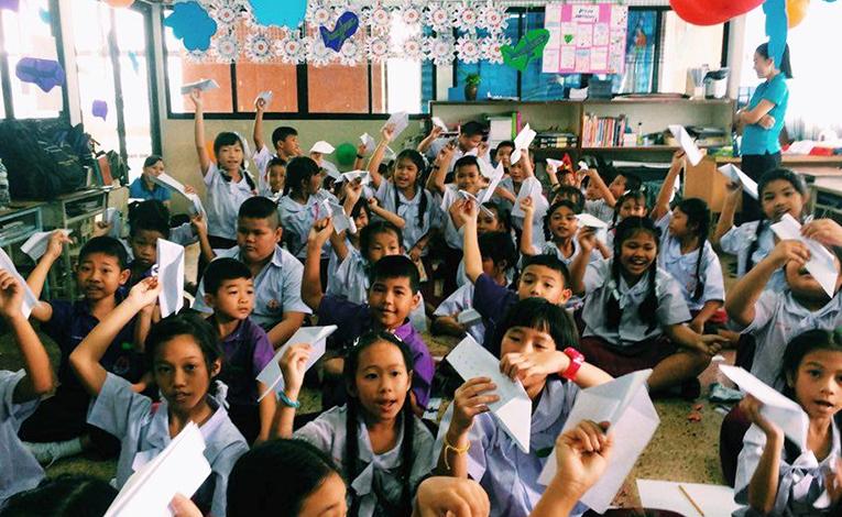 Thai children making paper planes