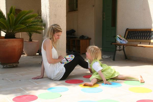 A mother playing twister with her daughter