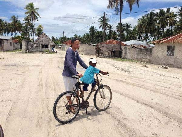 A volunteer giving a small a ride on his big bicycle