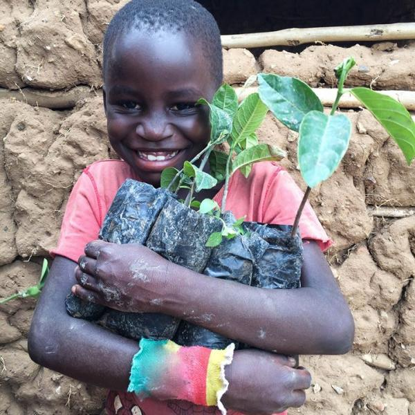 A happy student with his very own jackfruit sapling, ready to get planting!
