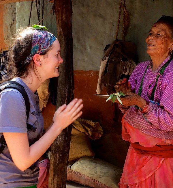 A volunteer shares a laugh with a Nepalese woman during a moment of cultural exchange.