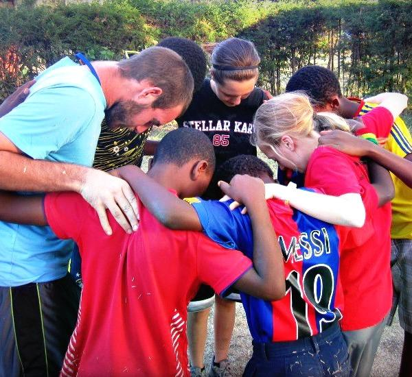Missionary praying with children in Ethiopia, Africa