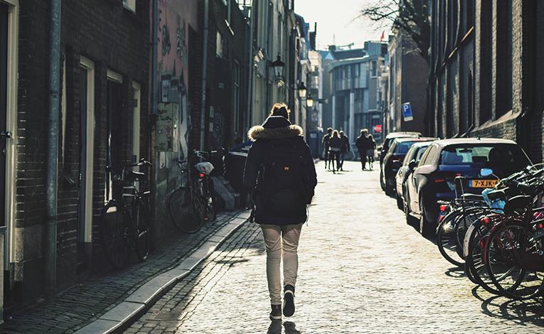 Girl walking down a narrow alleyway