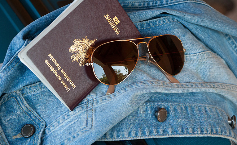 Passport and sunglasses on a jean jacket