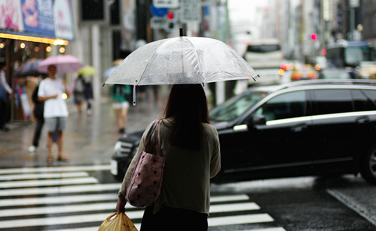 Woman crossing the street holding an umbrella