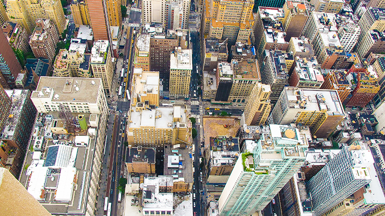 aerial view of a city with cars, traffic, and skyscrapers.