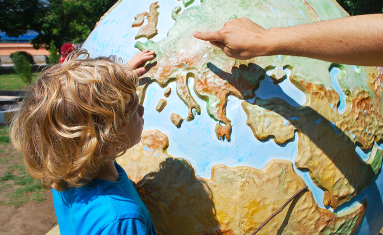 A parent showing the kid the map of the world