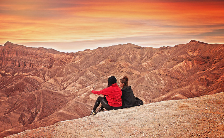Two girls sitting on a mountainside taking a selfie at sunset