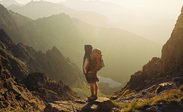 Hiker in shorts standing in a mountain pass