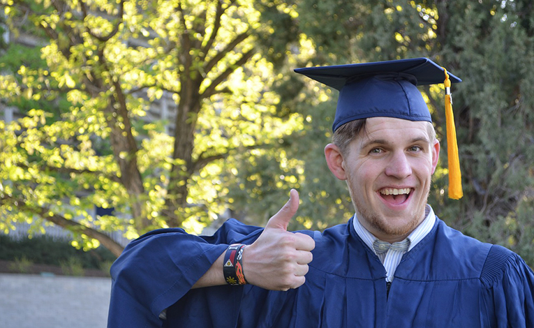 man in cap and gown giving a thumbs up
