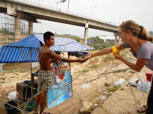 Girl giving a man a drink in Burma