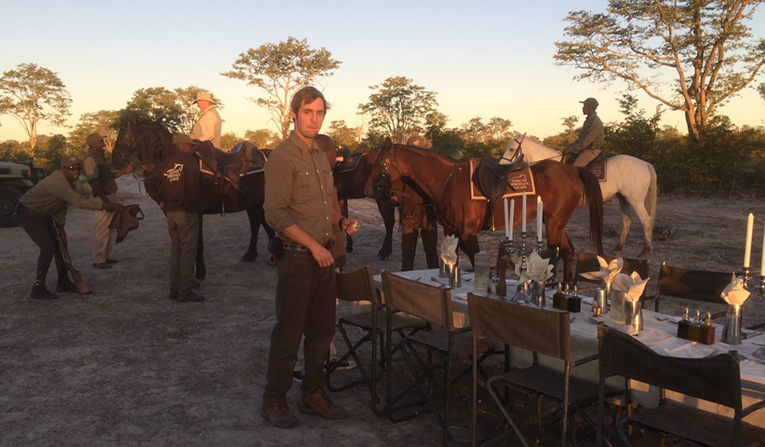 An intern sets up dinner for guests at African Horseback Safaris