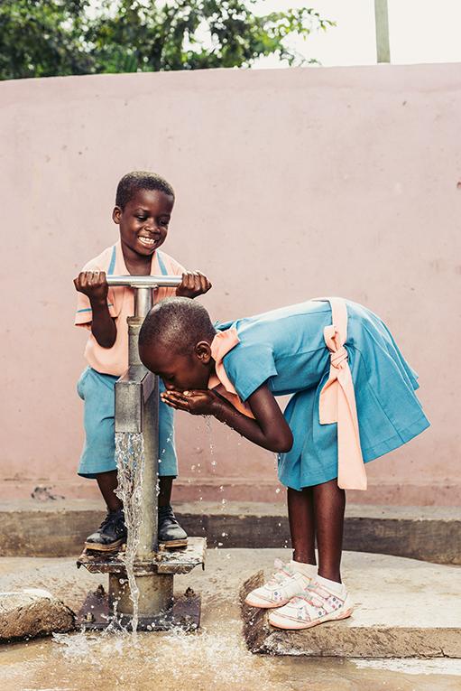 Girls using a water pump in Ghana