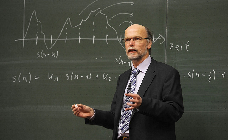 Professor lecturing in front of a chalkboard