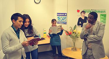 Students reading books while an instructor watches them.