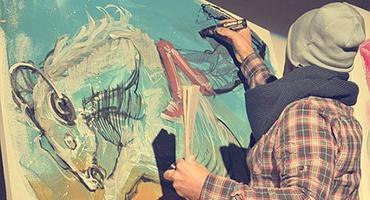 A male artist painting on a large canvass.
