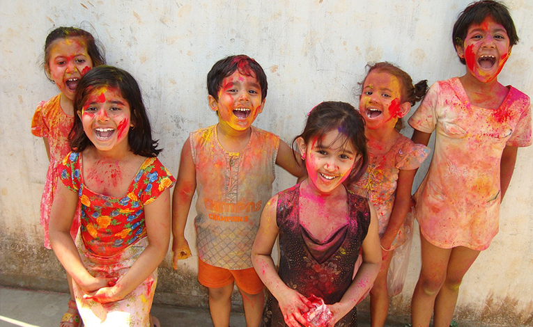 Children covered with bright paint during Holi in India