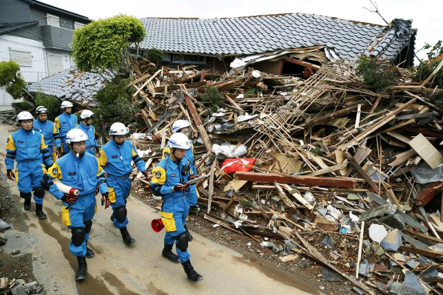 Police officers check a collapsed house after an earthquake in Mashiki town, Kumamoto prefecture, Southern Japan.