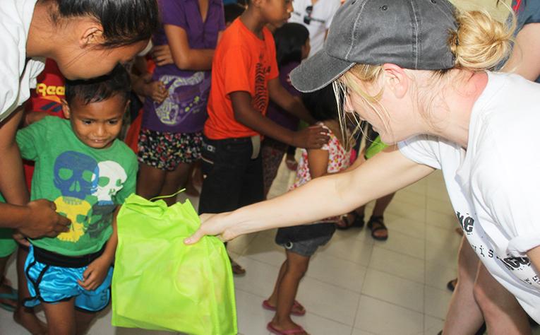 Volunteer handing some goodies to a kid