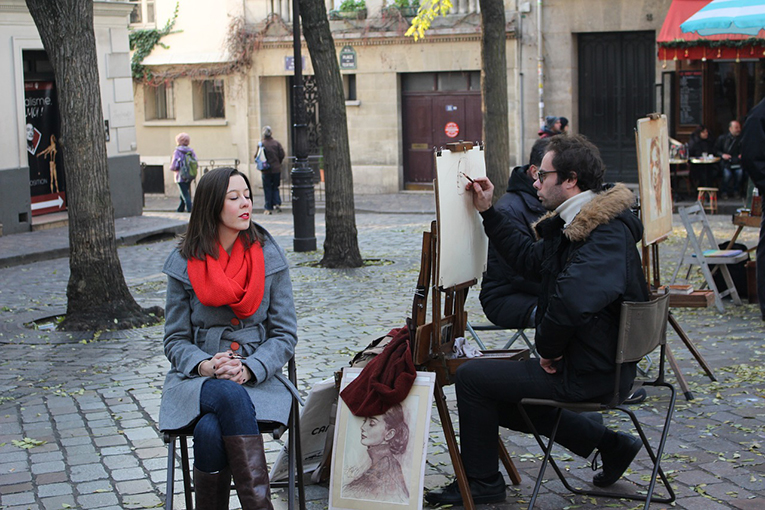 A street artist painting a portrait of a lady in Montmartre, Paris