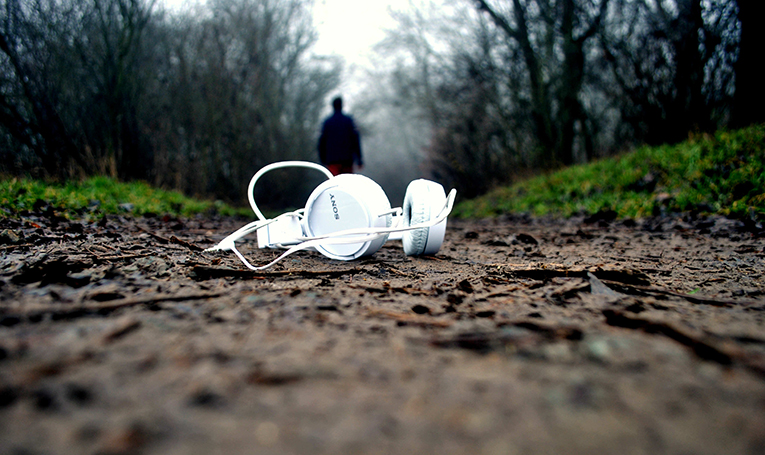 Noise-canceling headphones lying in the middle of an outdoor path