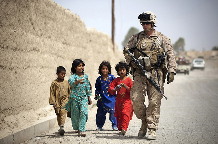 Solider walking with children in the Middle East
