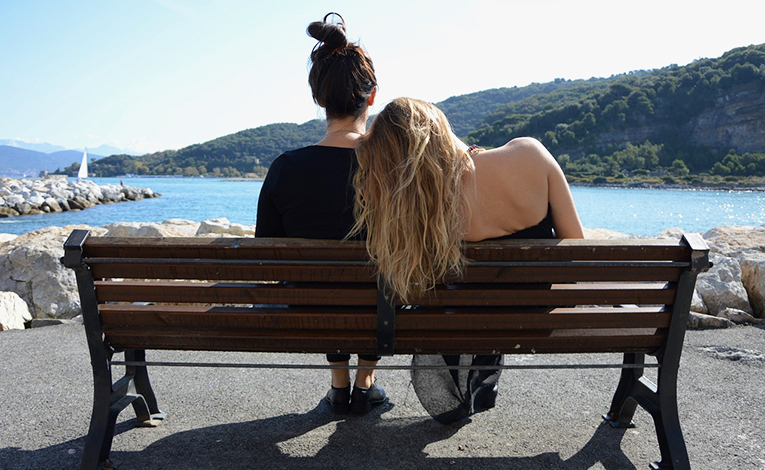 Best friends sitting on bench in Italy.
