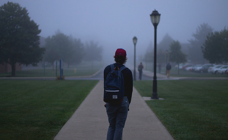Boy walking on a college campus