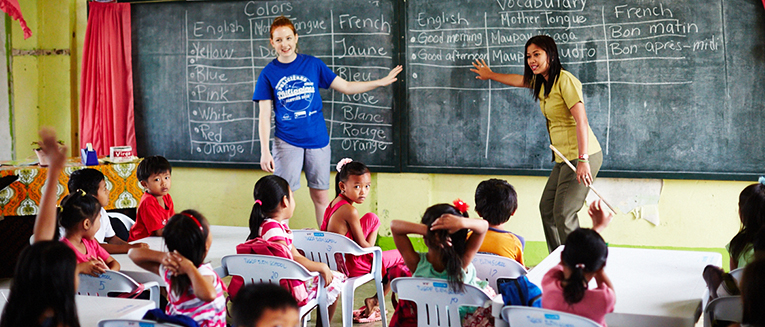 A volunteer and a local teacher teaching English to the class