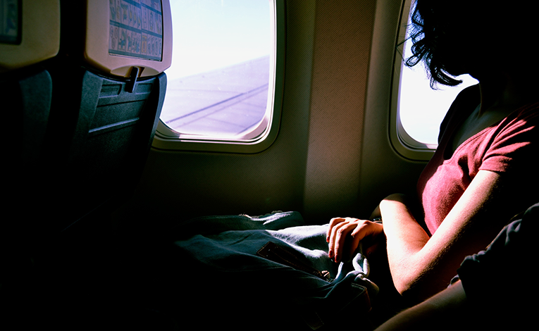 Young girl on airplane looking out window