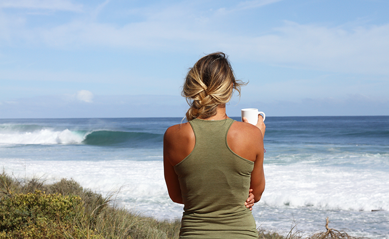 Woman with a mug looking at the ocean